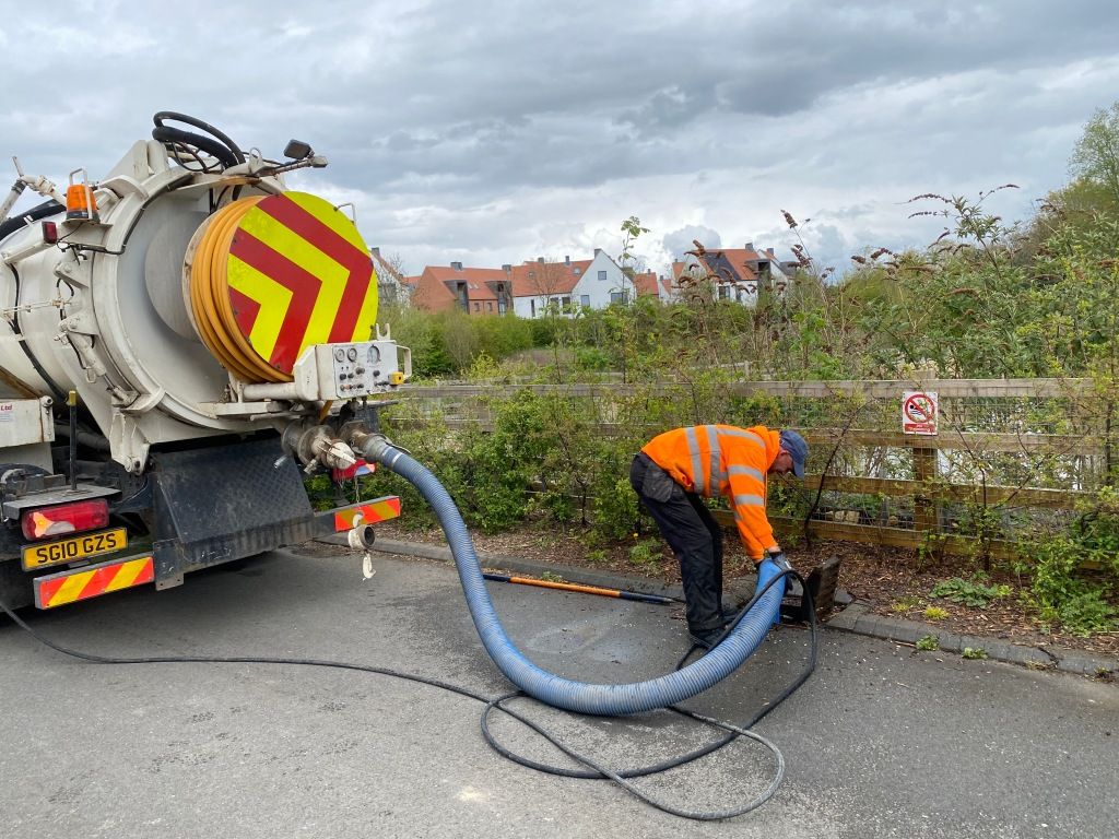 Man in Hi-viz jacket working a large bore hose down a road drainage gulley.